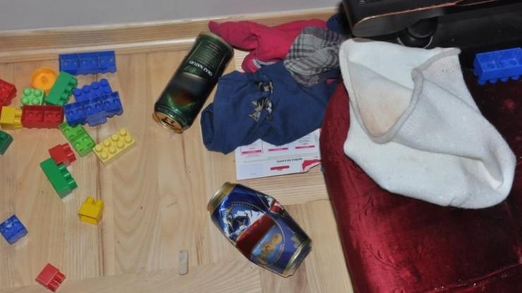 Zabawki obok pustych puszek po piwie. Pijani rodzice opiekowali się dziećmi