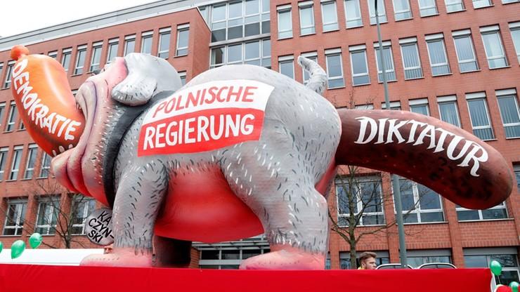 """Polski rząd jako pies pożerający kiełbasę z napisem """"demokracja"""". Karnawał po niemiecku"""